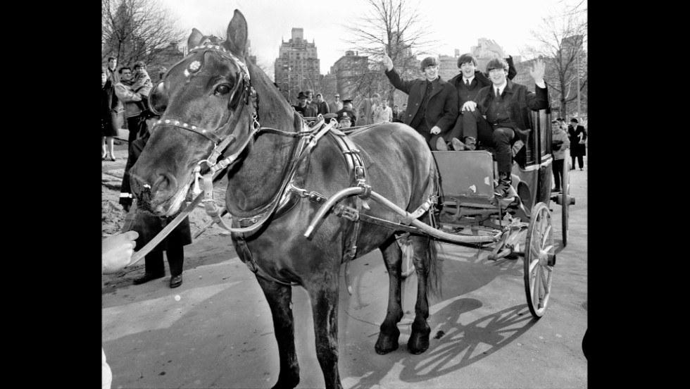 Ringo Starr, Paul McCartney and John Lennon wave from a hansom cab in Central Park the day after the Beatles' arrival in the United States for the first time. George Harrison was off nursing a sore throat.