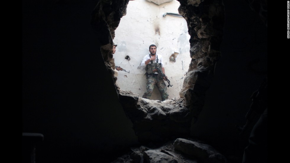 A rebel fighter holds his position in a damaged building during clashes with government forces in Deir Ezzor on Monday, November 11.