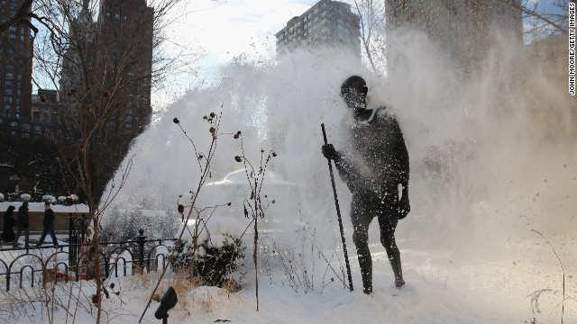 A snow blower clears a sidewalk next to a statue of Mahatma Gandhi at Union Square Park in New York City on January 22.
