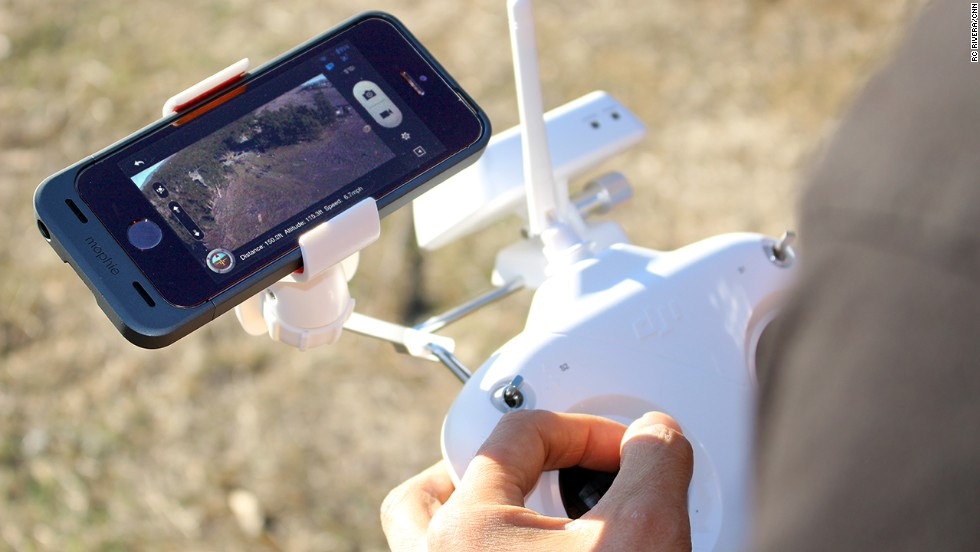 "Live video from a <a href=""http://www.dji.com/product/phantom/"" target=""_blank"">DJI Phantom</a> drone is displayed on an iPhone app. The Phantom controller has a special mount for the smartphone."