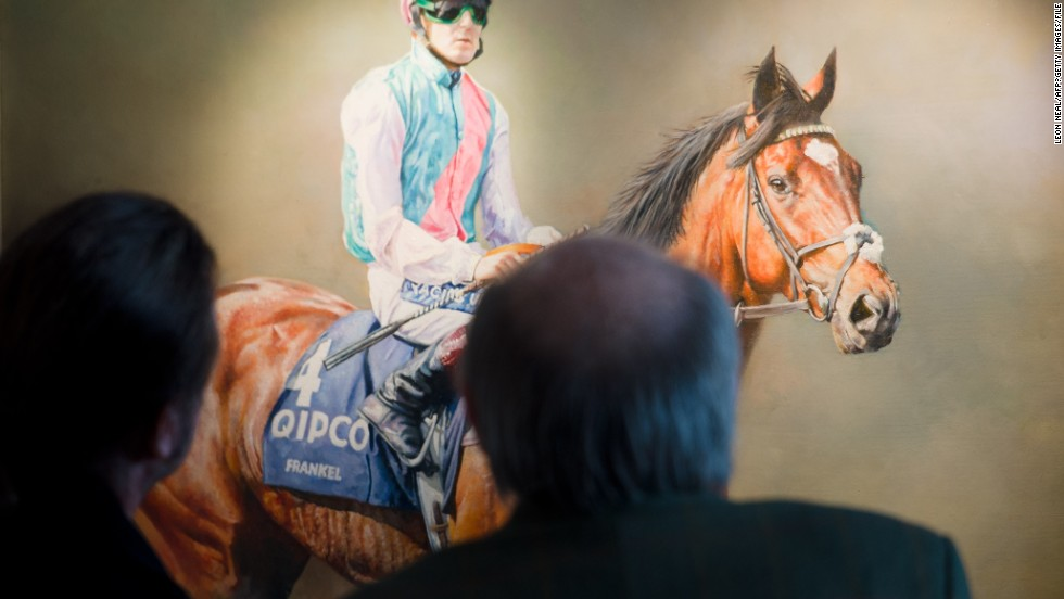 Such was his success Frankel was even immortalized in paintings. Here racegoers look at a painting of racehorse Frankel at Ascot.