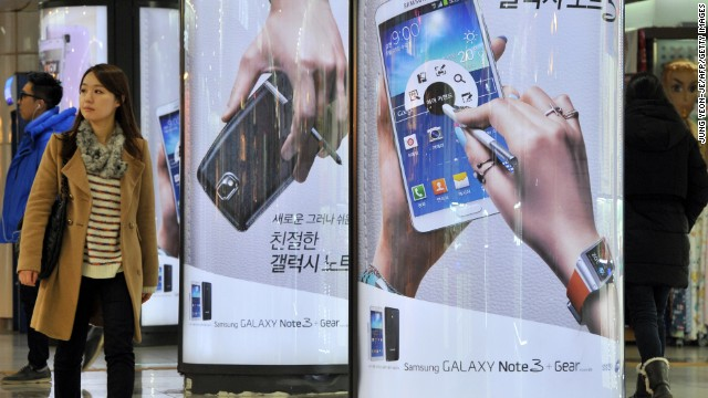A woman in Seoul walks past signs advertising the Galaxy Note 3, the smartphone from Korean manufacturer Samsung.
