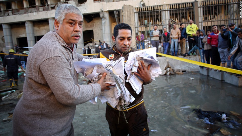 Men carry documents away from the site of the explosion.
