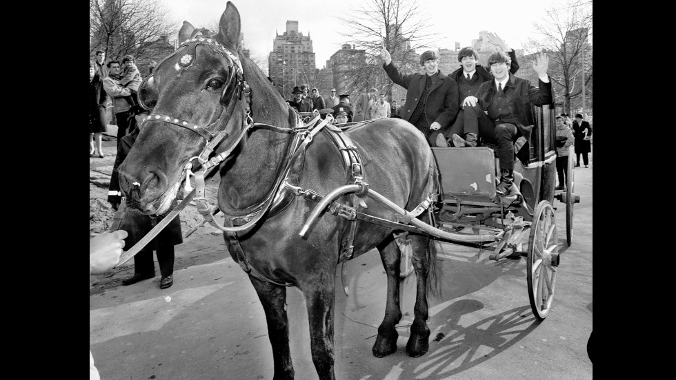Three of The Beatles -- from left, Ringo Starr, Paul McCartney and John Lennon -- wave from a horse-drawn carriage in New York's Central Park on February 8, 1964. George Harrison was off resting a sore throat.