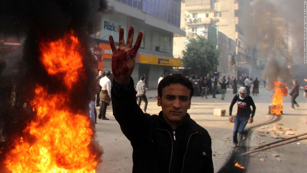 A supporter of the Muslim Brotherhood flashes a four-fingered salute next to burning tires allegedly set ablaze by protesters during clashes with security forces.