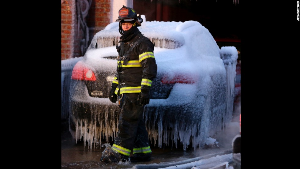 A North Hudson County firefighter walks in front of an ice-covered vehicle near a building where a six-alarm fire was put out January 24 in Union City, New Jersey.