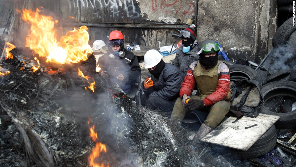 Protesters sit behind a barricade in Kiev on January 28.