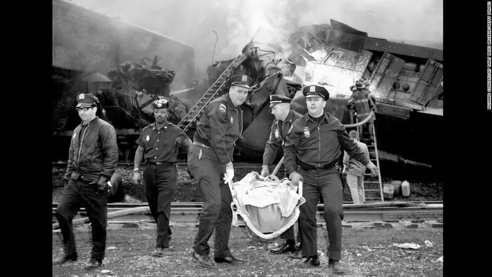 Patrolmen carry one of the dead from the wreckage caused when two trains crashed in a New York freight yard on May 22, 1967. Six crew members died and four more were injured.