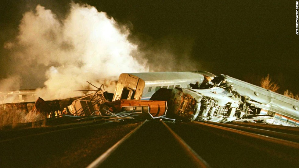 Rescue workers search the wreckage of a derailed Amtrak passenger train March 16, 1999, after it collided with a semi-trailer truck in Bourbonnais, Illinois, about 50 miles south of Chicago. Eleven people were reported dead and more than 100 were injured.