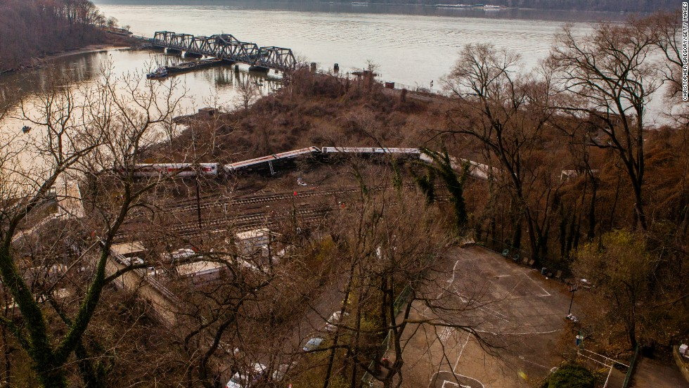 A Metro-North commuter train lies in the brush near the Hudson River after it derailed just north of the Spuyten Duyvil station December 1, 2013, in the Bronx borough of New York City. Four died and scores were injured after the seven-car train left the tracks as it was heading to Grand Central Terminal along the Hudson River line.
