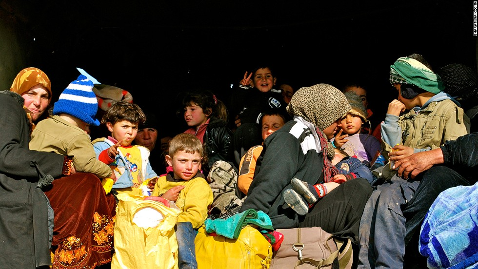 Exhausted refugees pile into a truck for the half hour trip to the border camp, where they will be given food and water and processed.