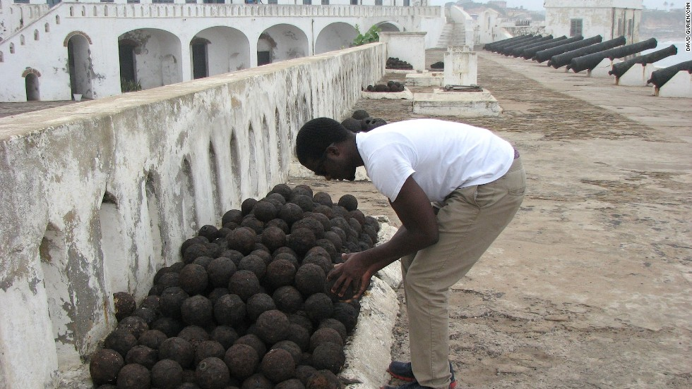 Clark examines original cannonballs, stacked near the defense cannons at Cape Coast Castle. The Dutch considered the castle, with its high, thick walls and fierce guns impossible to capture, even though they occupied Elmina castle just a few kilometers away.