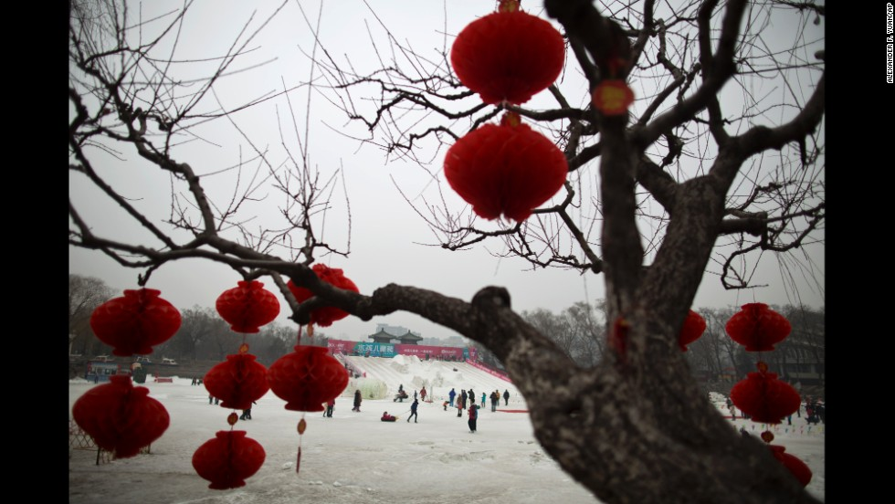 People play on an iced lake covered with artificial snow at Longtan Park in Beijing on February 1.