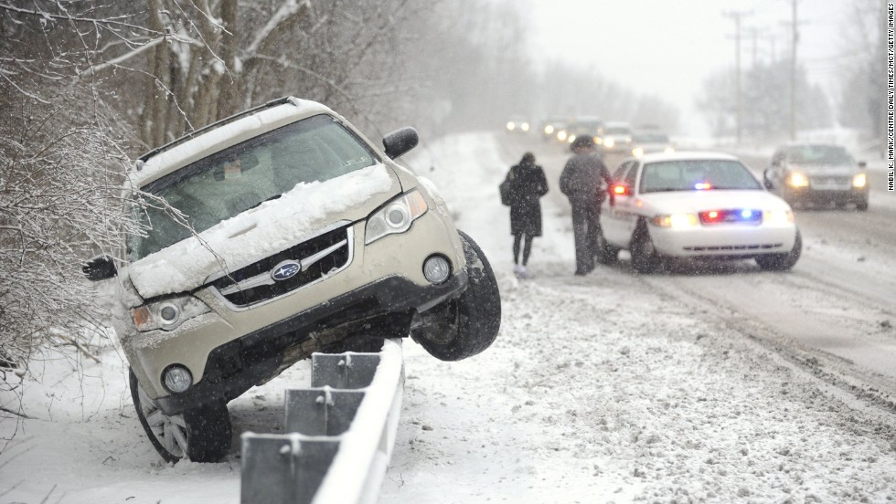 A police officer walks a woman to his vehicle after her car slid off the road and was stranded on top of a guardrail February 3 in State College, Pennsylvania.