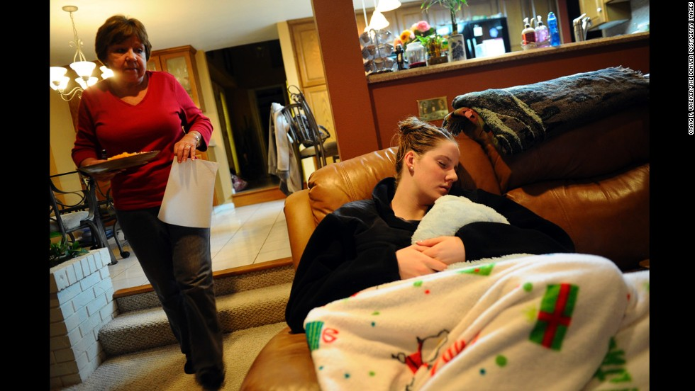 U.S. swimmer Missy Franklin falls asleep on the sofa while her mother, D.A., prepares dinner at their home in Colorado in 2011.