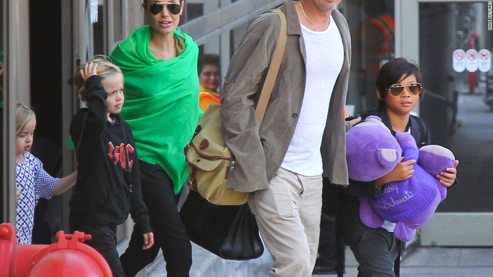 Brad Pitt and Angelina Jolie round up the troops as they de-plane in Los Angeles on February 5.