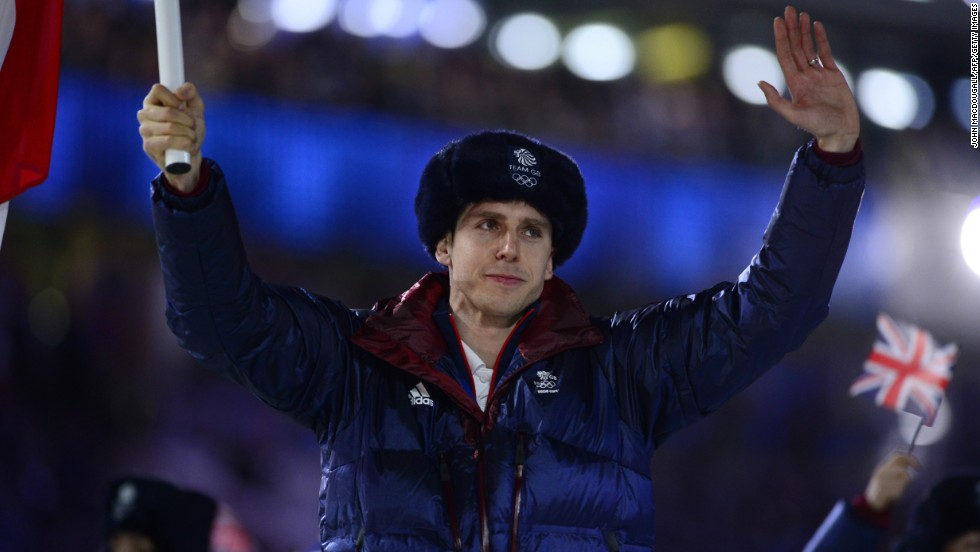 Great Britain's flag bearer, short-track speed skater Jon Eley, waves as he leads the British delegation.