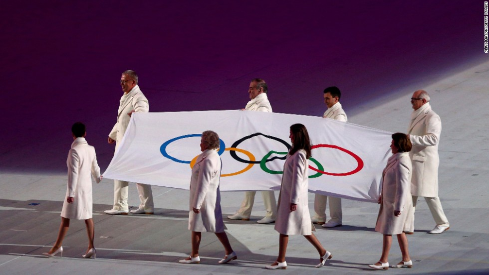 Olympic flag bearers carry the flag onto the floor during the opening ceremony.