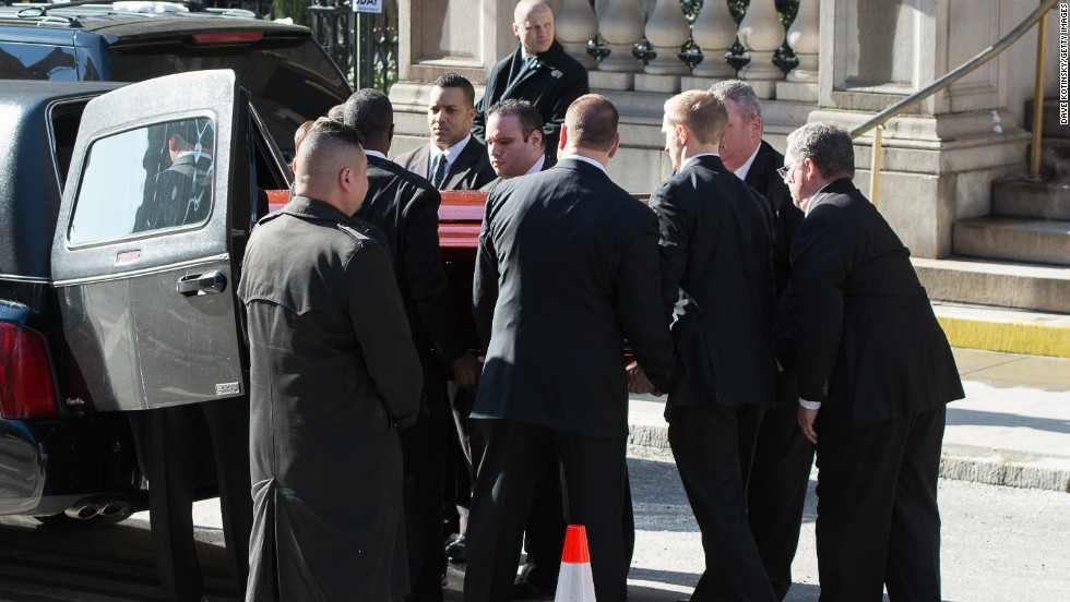 Pallbearers lift Hoffman's casket into the back of a hearse.