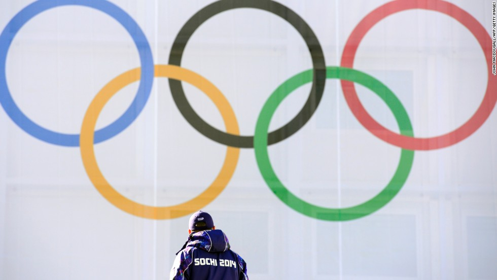 A security member walks by Olympic rings at the RusSki Gorki Ski Jumping Centre in Rosa Khutor on February 6.