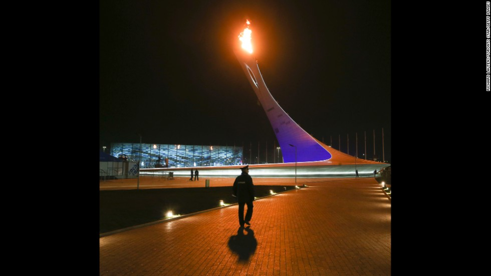 A security officer walks around the Olympic cauldron after the opening ceremony on Friday, February 7.