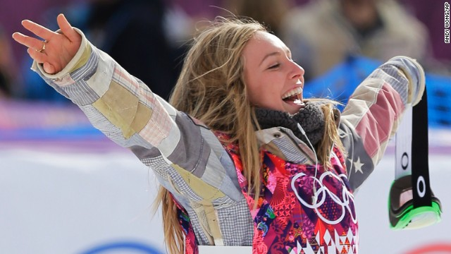 Jamie Anderson of the United States celebrates on the way to the flower ceremony after winning the women's snowboard slopestyle final at the 2014 Winter Olympics, Sunday, Feb. 9, 2014, in Krasnaya Polyana, Russia. (AP Photo/Andy Wong)