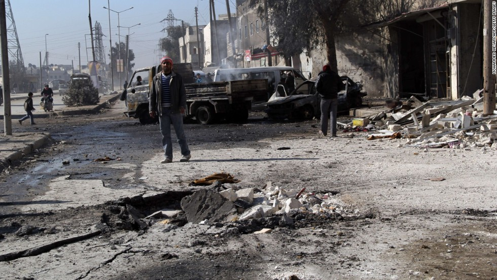 A man stands next to debris in the road following a reported airstrike by Syrian government forces in Aleppo on February 8.
