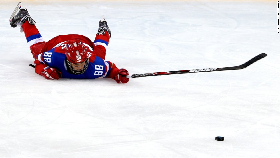 Yekaterina Smolina of Russia slides on the ice after being checked by Anja Weisser of Germany during their ice hockey game February 9.