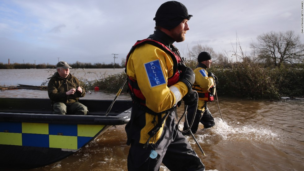 Police tow a Moorland, England, resident back to his flooded home to retrieve possessions on Sunday, February 9.