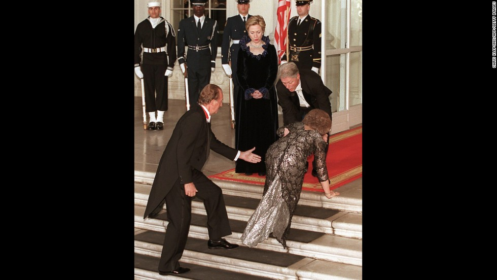 Queen Sofia of Spain is aided by President Bill Clinton  and her husband, King Juan Carlos of Spain, as she trips during the arrival for a state dinner on February 23, 2000. First lady Hillary Clinton watches in the background.