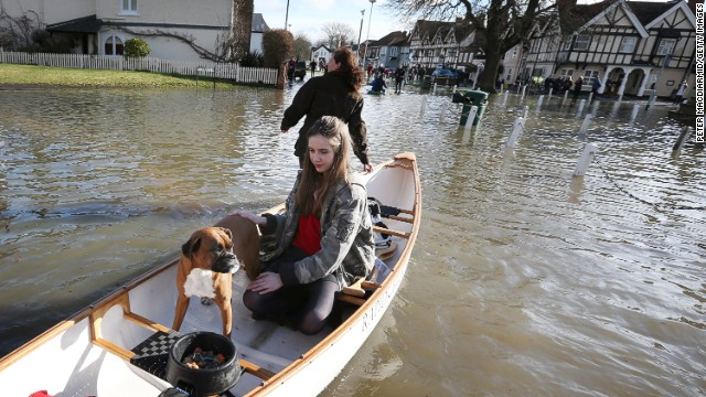 People evacuate homes after the River Thames burst its banks on Monday in Datchet, England.