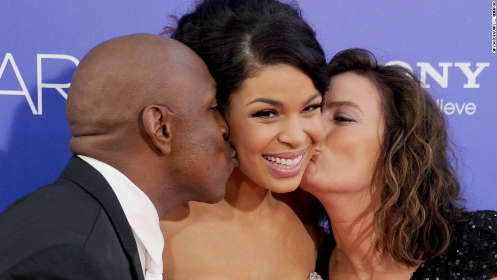 "Actress and recording artist Jordin Sparks receives a kiss from her dad, former football player Phillippi Sparks, and mom, Jodi Sparks, at the premiere of ""Sparkle."""