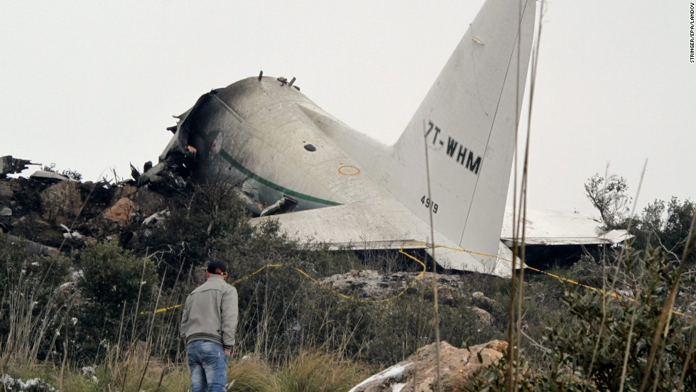 A man surveys the damage after a military plane crashed in the mountains of eastern Algeria on Tuesday, February 11. Rescue workers recovered at least 77 bodies and found one survivor, officials said.