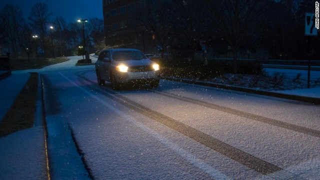 A motorist drives on a snow-and-ice-covered street in Johns Creek, Georgia, on February 12.
