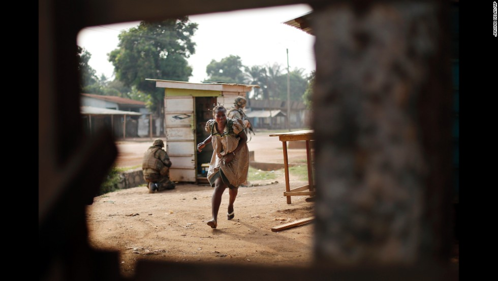 A woman runs for cover as heavy gunfire erupts in the Miskin district of Bangui on Monday, February 3.