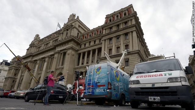 TV broadcast vans remain parked in front of Argentina's Supreme Court Palace in Buenos Aires on October 29, 2013 after it upheld as constitutional a controversial law that would force the country's largest media group, Clarin, to divest some of its units. Clarin, which has been locked in conflict with President Cristina Fernandez de Kirchner, had challenged the validity of the media law, passed four years ago by the Argentine Congress. But by a vote of six to seven, the top court ruled that it was constitutional, upholding an antitrust clause that will force Clarin to divest most of its lucrative cable television operations. AFP PHOTO / JUAN MABROMATA (Photo credit should read JUAN MABROMATA/AFP/Getty Images)