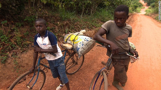 Young workers carry sacks of cocoa beans on their bikes in Ivory Coast