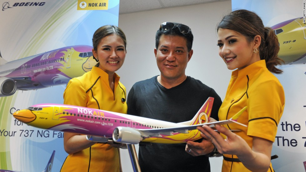 Nok Air's chief executive Patee Sarasin, flanked by the Thai budget airlines' flight attendants. Nok Air has ordered 15 Boeing 737 jets in a deal valued at $1.45 billion.
