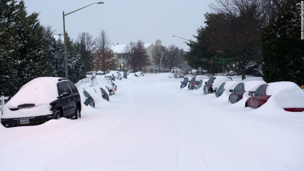 Cars sit covered in snow on a street in Manassas, Virginia, on February 13.