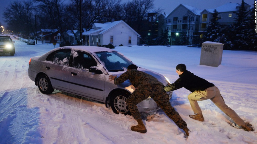 People help push a car stuck in the snow February 13 in Alexandria, Virginia.