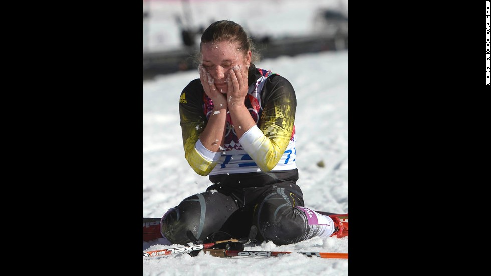Cross-country skier Alexandra Camenscic of Moldova wipes her face with snow at the finish line of the women's 10-kilometer classic on February 13.
