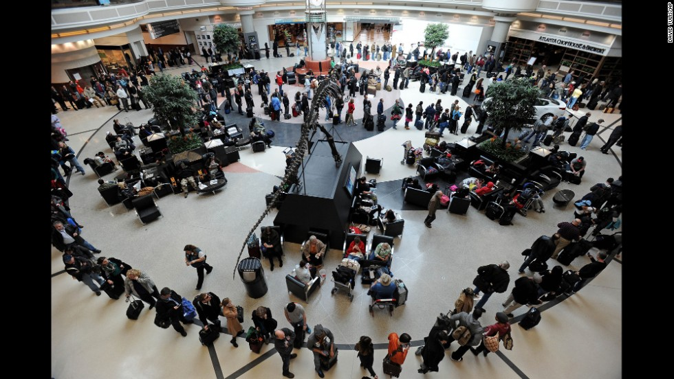 A long line of travelers winds around the atrium of Hartsfield-Jackson Atlanta International Airport on February 13 as people attempt to catch flights previously canceled because of the massive winter storm.