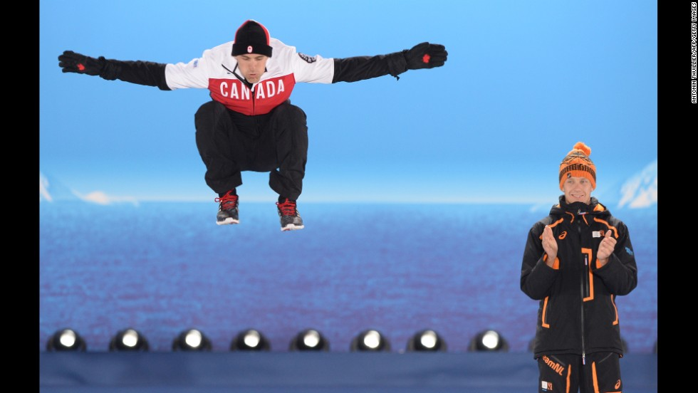 Canadian silver medalist Denny Morrison jumps next to Dutch gold medalist Stefan Groothuis during the medal ceremony for the men's 1,000-meter speedskating event.