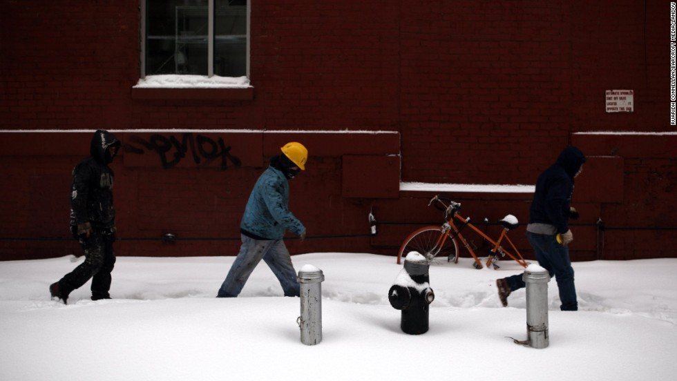 People walk through the snow on February 13 in Brooklyn, New York.