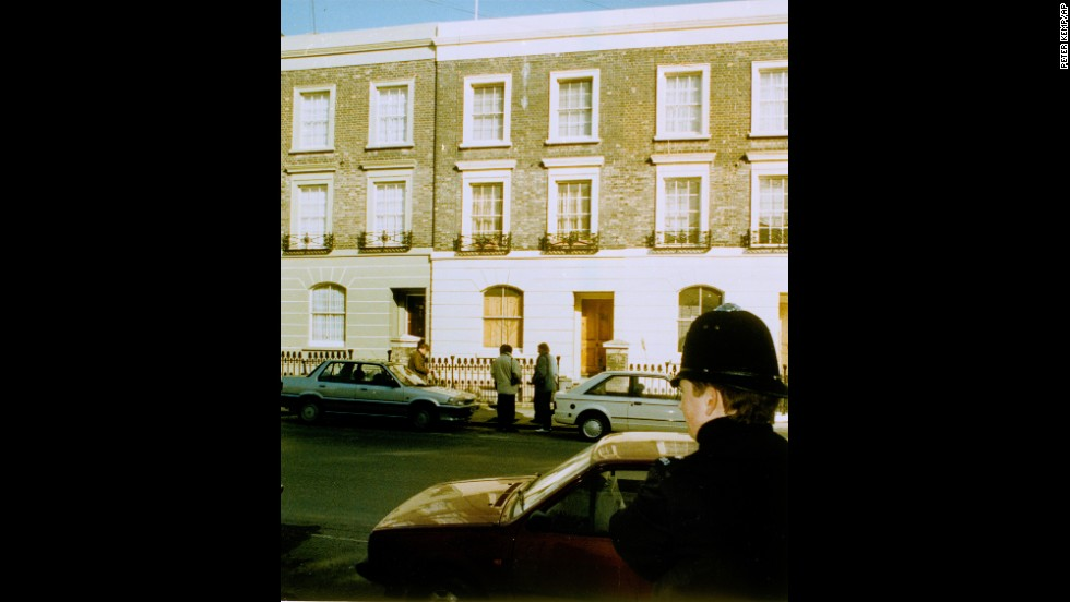Reporters stand outside Rushdie's London home on February 16, 1989, as a police officer watches from across the street.