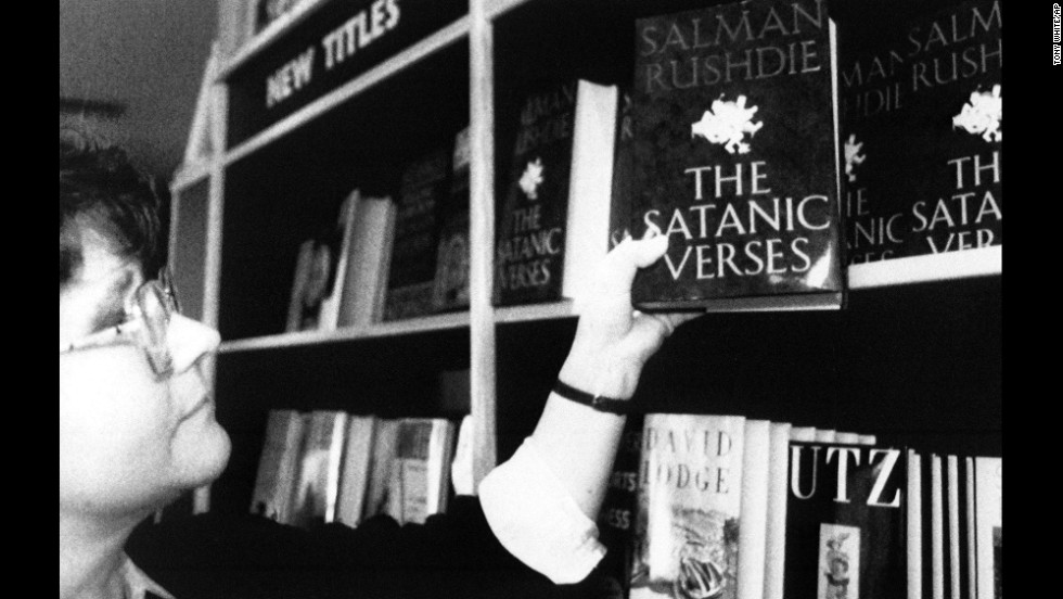 "A shop assistant places a copy of ""The Satanic Verses"" onto a bookshelf in a London bookshop on February 16, 1989. The shop took delivery of 20 copies in the morning and sold out in a few hours. High sales of the book aided Rushdie's ability to stay hidden."