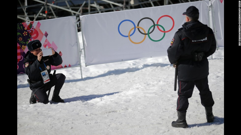 A police officer has his photo taken in front of the Olympic rings Friday, February 14, in Sochi, Russia.