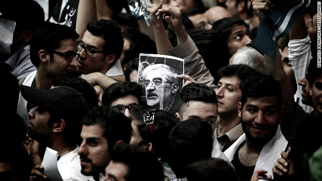 A portrait of opposition leader Mir Hossein Mousavi is held during a campaign rally in Tehran on June 10, 2013.