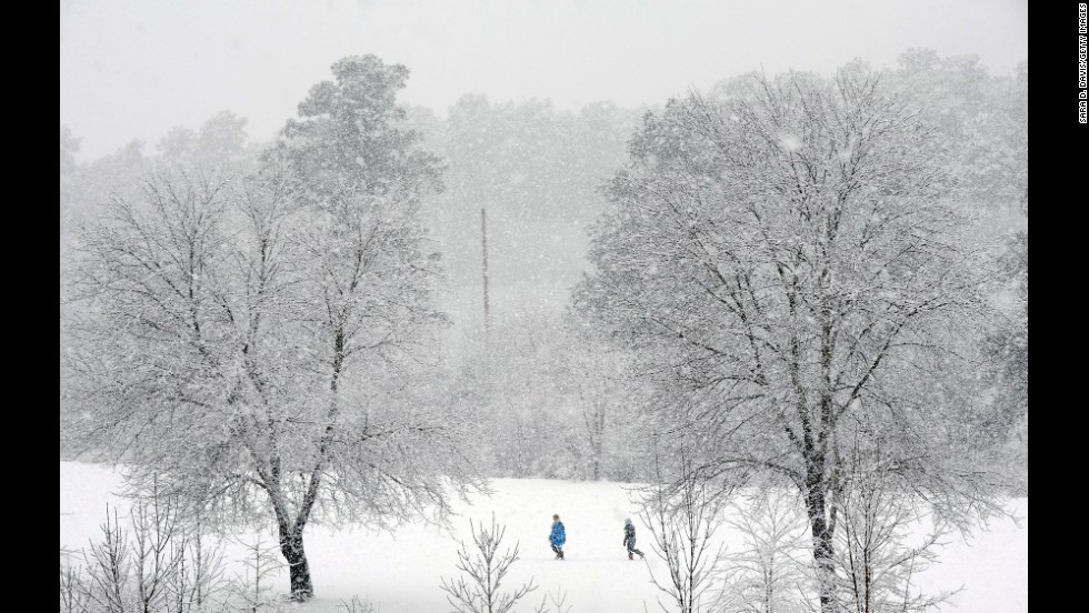 People trek through a golf course in Durham, North Carolina, as heavy snow falls on Thursday, February 13.