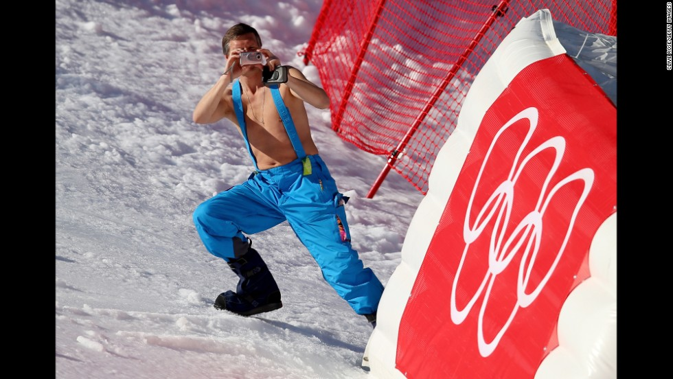 A shirtless volunteer takes a picture during the women's super-G on February 15.